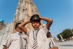 白色衬衣的Schoolkids在古老天主教附近使用 免版税库存照片