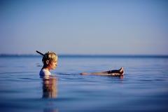 白色衬衣谎言后面的少妇和放松在蓝色海水时尚射击 免版税库存照片