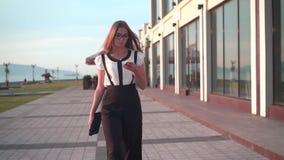 白色衬衫和玻璃的女商人走在街道上在一座现代办公楼附近和谈话在电话 股票视频