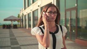 白色衬衫和玻璃的女商人走在街道上在一座现代办公楼附近和谈话在电话 股票录像