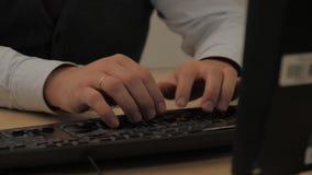 白色衬衫和背心的人在书桌和类型后坐黑键盘 股票视频