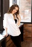 白色衬衫和黑色裤子的美丽的年轻欧洲妇女在窗口附近站立并且看对照相机 图库摄影