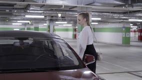 白色衬衫和黑裙子的走的beautifu妇女在undeground停车场 股票录像