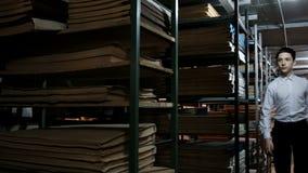 白色衬衫奔跑的一个少年在与文件的架子之间在图书馆里 有老文学的书架 档案室 股票录像