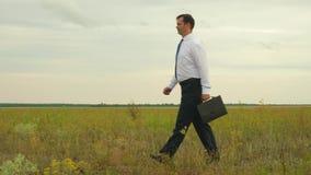 白色衬衫的一位农艺师在与黑公文包奔跑的蓝色领带通过一次重要会议的领域 股票视频