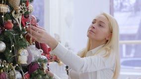 白色衬衫的一美女装饰一棵大圣诞树 股票视频