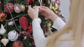 白色衬衫的一美女装饰一棵大圣诞树 股票录像