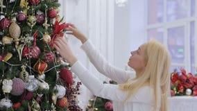 白色衬衫的一美女装饰一棵大圣诞树 影视素材
