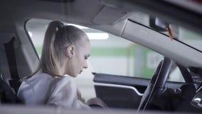 白色衬衫的年轻女人从undeground车库走出去并且进入汽车 股票录像