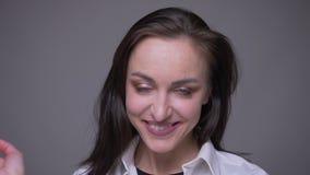 白色衬衫的微笑和修理她的头发的成人可爱的白种人女性特写镜头画象看照相机 影视素材
