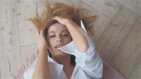 白色衬衫的美丽的年轻女人在地板上说谎 股票录像