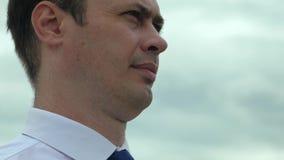 白色衬衫调查的一个成人严肃的人反对阴沉的灰色天空背景的距离  特写镜头 股票视频
