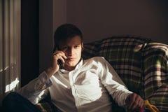 白色衬衫谈话的强壮男子在扶手椅子的智能手机 免版税库存照片