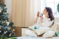 白色被编织的佩带的愉快的妇女为圣诞节在家放松 免版税库存图片