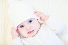 白色被编织的毛线衣的在一白色缆绳的婴孩和帽子编织毯子 免版税库存照片