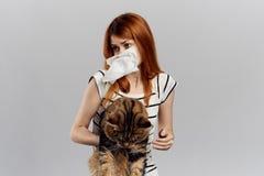 白色被隔绝的背景的美丽的少妇拿着一只猫 免版税库存图片