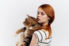 白色被隔绝的背景的年轻美丽的妇女拿着一只猫,宠物,动物 图库摄影