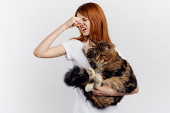 白色被隔绝的背景的年轻美丽的妇女拿着一只猫,过敏 免版税库存照片