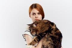 白色被隔绝的背景的年轻美丽的妇女拿着一只猫 免版税图库摄影