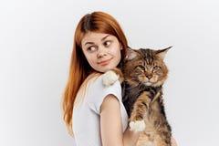 白色被隔绝的背景的年轻美丽的妇女拿着一只猫 库存照片