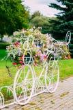白色装饰自行车停车处在庭院里 免版税库存照片