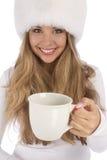 白色裘皮帽的可爱的女孩给白色杯子 免版税图库摄影