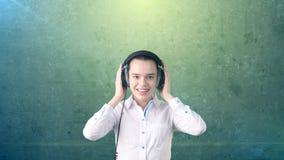 白色裙子放松的听的女实业家到在立体声耳机的音乐有有福的微笑的 被隔绝的背景 免版税库存照片
