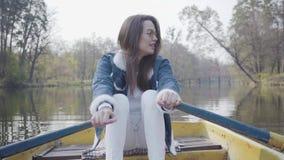 白色裤子、牛仔裤夹克和太阳镜桨的俏丽的年轻魅力妇女在河的黄色小船,看 股票录像
