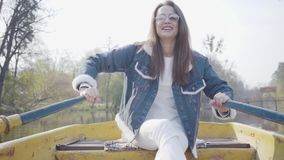 白色裤子、牛仔裤夹克和太阳镜桨的俏丽的微笑的魅力妇女在河的黄色小船 影视素材