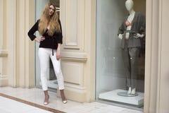 白色裤子和条绒夹克的美丽的白肤金发的妇女 免版税库存图片