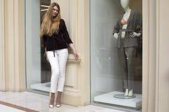 白色裤子和条绒夹克的美丽的白肤金发的妇女 库存照片