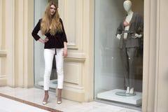 白色裤子和条绒夹克的美丽的白肤金发的妇女 库存图片