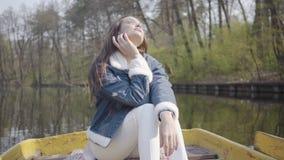 白色裤子和牛仔裤夹克的俏丽的魅力妇女在河的小船,享用太阳 r 影视素材