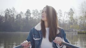 白色裤子和牛仔裤夹克的a俏丽的魅力妇女在河的小船用浆划,看  女孩学会 股票录像