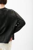 白色裤子和黑皮夹克的少妇 免版税库存照片