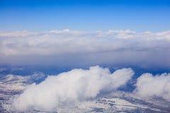 白色覆盖垂悬在蓝天的背景在多雪的山 从平面` s窗口的空中照片 库存图片