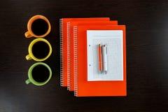 白色说谎在与橙色和白色笔的一张黑褐色木桌上的写生簿和橙色笔记本在咖啡旁边 库存图片