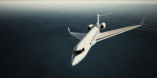 白色豪华普通设计私人喷气式飞机飞行照片在天空的在晚上 蓝色海洋背景 商务旅游图片 图库摄影