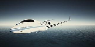 白色豪华普通设计私人喷气式飞机飞行照片在天空的在水表面下 蓝色海洋背景 事务 免版税库存图片