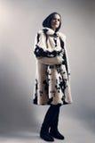 白色貂皮多斑点的皮大衣的妇女 库存照片