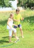 白色走的女孩通过喷水隆头 库存图片