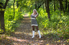 白色起动的美丽的聪慧的金发碧眼的女人在森林小径 库存图片