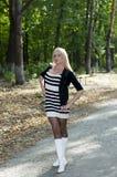 白色起动的美丽的金发碧眼的女人在一条道路在公园 免版税库存图片