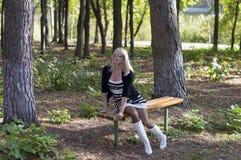 白色起动的美丽的金发碧眼的女人在一条长凳在公园 库存图片