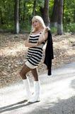 白色起动的美丽的金发碧眼的女人在公园走 库存照片
