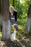 白色起动的美丽的金发碧眼的女人在树后 库存图片