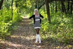 白色起动的美丽的金发碧眼的女人在森林小径,秋天 图库摄影