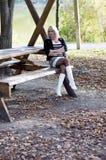 白色起动的美丽的金发碧眼的女人坐一个长木凳 免版税库存照片