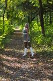 白色起动的金发碧眼的女人在森林小径 免版税库存图片