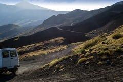 白色越野汽车绕过Etna火山的绝种火山口与黑熔岩的 库存图片